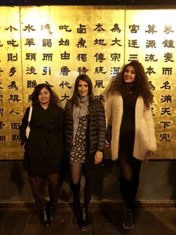 Enza with two friends in front of a wall covered in Chinese characters