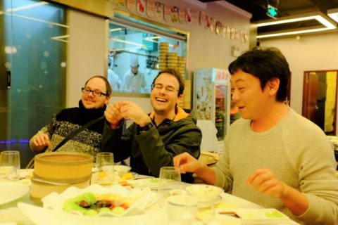 Teachers and students laughing at the table at a Beijing roast duck dinner