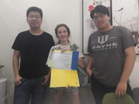 Perle holding up her HSK certificate next to her two teachers