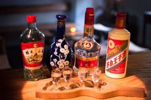 Selection of four bottles of Baijiu with glasses in the foreground.