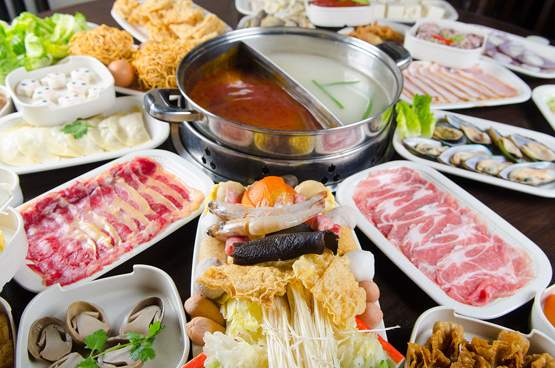 A selection of Chinese hot pot meats and vegetables surround the table