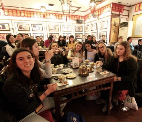 Italian students enjoying a Chinese dinner at a restaurant.