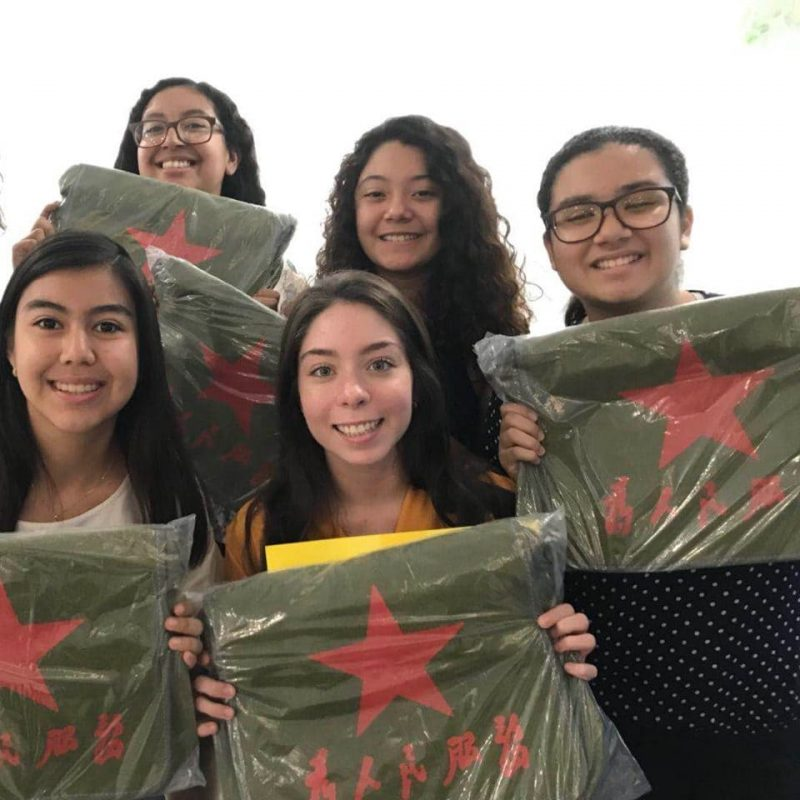 Four Mexican students holding up Chinese style bags