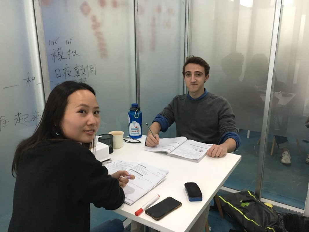Teacher and student sitting in classroom having individual Chinese class