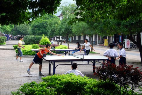 Several people playing ping pong outside in Beijing