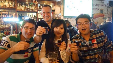 Students cheering with glasses of Baijiu at a bar in Shanghai
