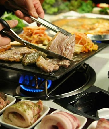 Up close photo of meat and vegetables on a Korean BBQ