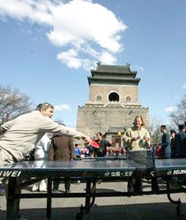 Two people playing ping pong outside in Beijing